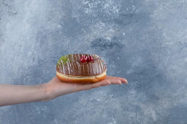 おいしいチョコレートを持っている女性の手が大理石の表面にドーナツを振りかけます。 無料写真