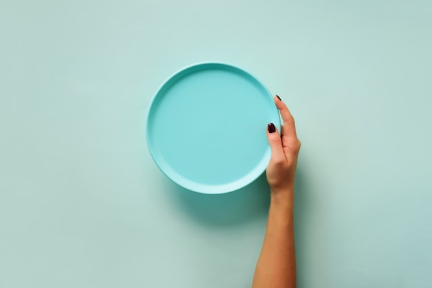 Female hand holding empty blue plate on pastel background with copy space. healthy eating, dieting concept. banner Premium Photo
