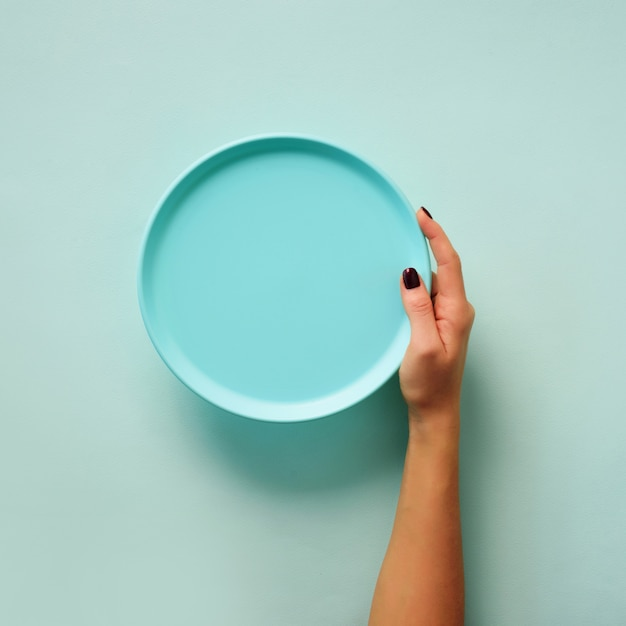 Female hand holding empty blue plate on pastel background with copy space Premium Photo