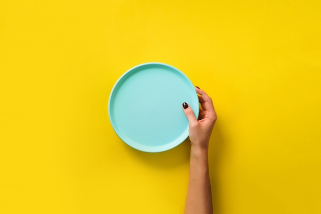 Female hand holding empty blue plate on yellow background with copy space. Premium Photo
