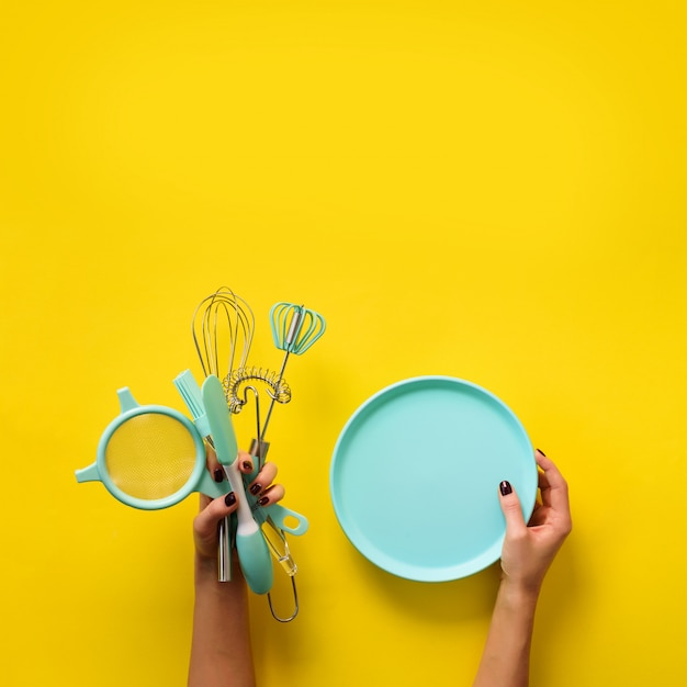 Female hand holding empty bowl on yellow background with copy space. Premium Photo