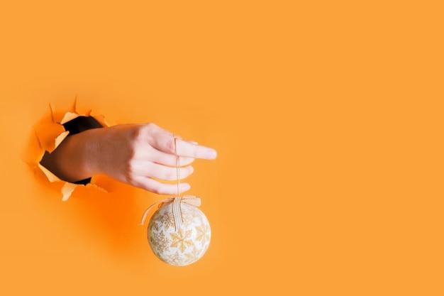 Female hand holding gold christmas decoration tree bauble through a hole on saffron . new year celebration Premium Photo