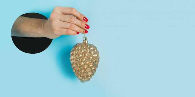 Female hand holding golden decorative cone through round hole in blue. invitation to christmas holiday party. Premium Photo