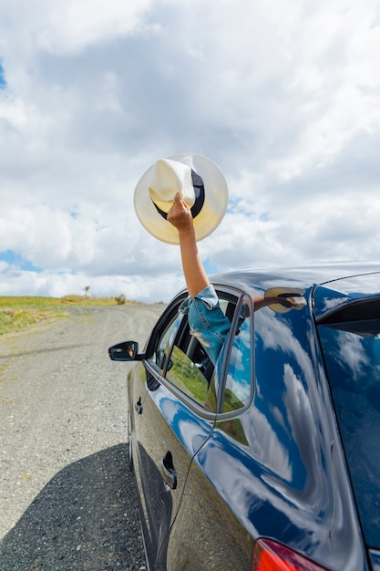 Female hand holding hat out of car window Free Photo