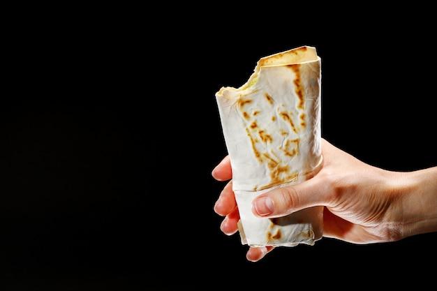 Female hand holding a kebab on a black background Premium Photo