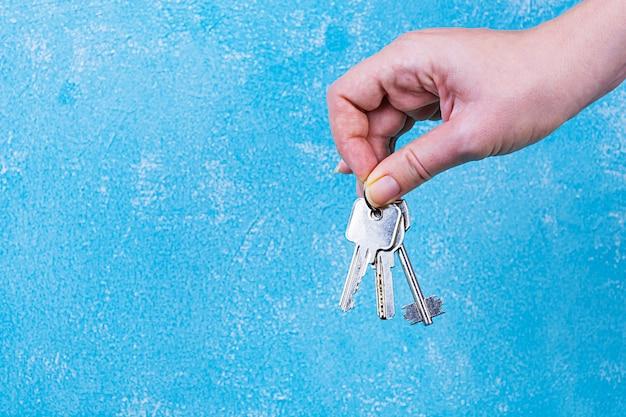 Female hand holding keys on blue wall Premium Photo