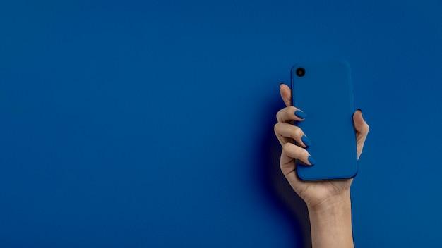 色の背景上の携帯電話を持っている女性の手 Premium写真