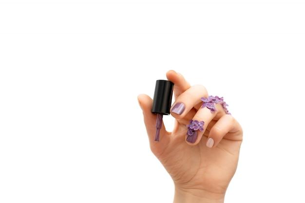 Женская рука держа фиолетовую бутылку лака для ногтей. концепция весны. Бесплатные Фотографии