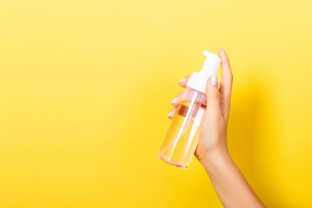 Female hand holding spray cream bottle of lotion. Premium Photo