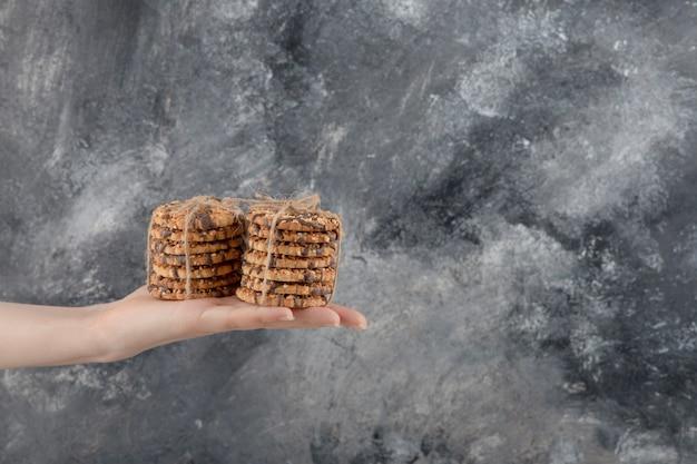 여성의 손을 대리석 배경에 오트밀 쿠키의 스택을 잡고. 무료 사진
