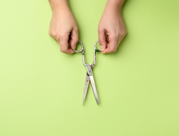 Женская рука держит старинные металлические ножницы изолированы Premium Фотографии