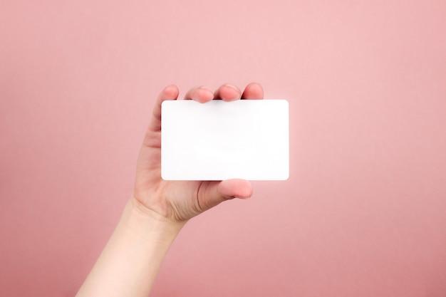 Женская рука держит белую визитку Premium Фотографии