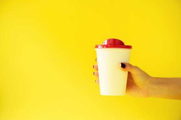 Female hand holding white paper mug on yellow background. Premium Photo