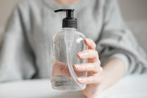 Female hand holds a bottle of a antibacterial gel, alcohol spray, liquid soap, antibacterial for coronavirus Premium Photo