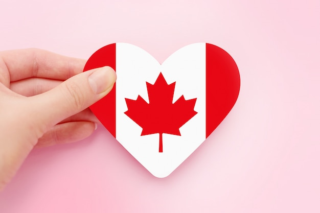 Female hand holds canada heart shaped paper flag isolated over pink space, canada day Premium Photo