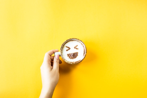 A female hand holds a cup of coffee on which is drawn emoji laughter Premium Photo