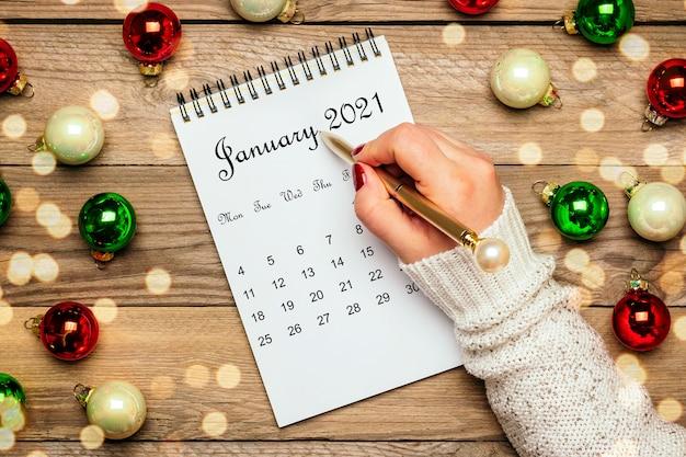 Female hand holds pen, open calendar january 2021, christmas decor on wooden table Premium Photo