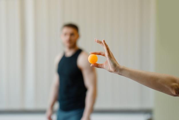 女性の手は、ピンポンボール、背景にスポーツウェアの男、ジムで卓球トレーニングゲームを保持しています。 Premium写真