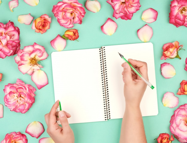 Female hand holds white pen over empty white sheet of paper Premium Photo
