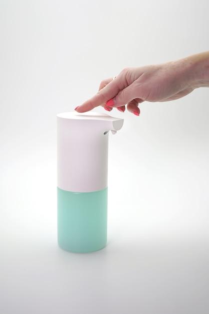 女性の手には、孤立した壁に自動ディスペンサー、消毒剤が含まれています。手の消毒、コロナウイルスのパンデミックの予防 Premium写真