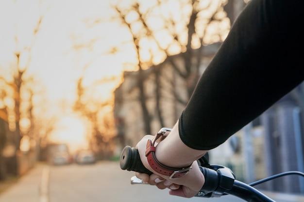 Женская рука на руле велосипеда на закате на улице. современный здоровый образ жизни Premium Фотографии