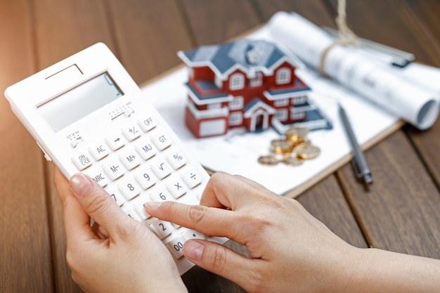 A female hand operating a calculator in front of a villa house model Free Photo