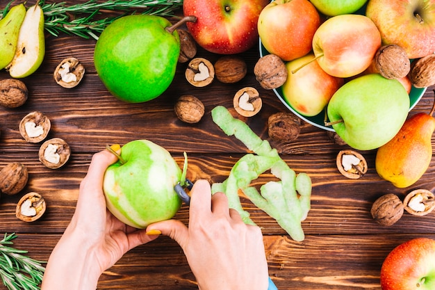 Female hand peeling green apple with peeler Free Photo