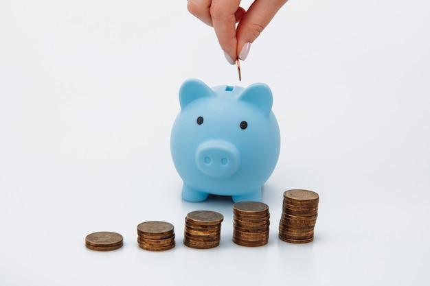 Женская рука положить монету в синей копилке. концепция экономии денег Premium Фотографии