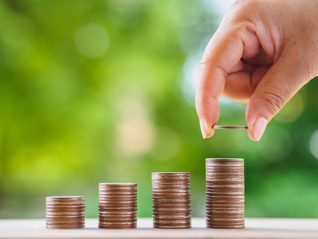 Female hand putting money coin stack growing business Premium Photo