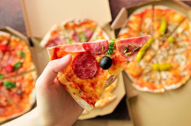 Female hand taking slice of fresh pizza from delivery box. top view, dark background. junk food Premium Photo