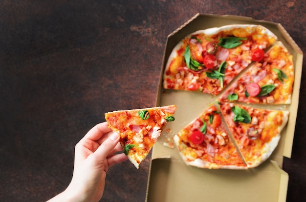 Female hand taking slice of fresh pizza from delivery box. Premium Photo