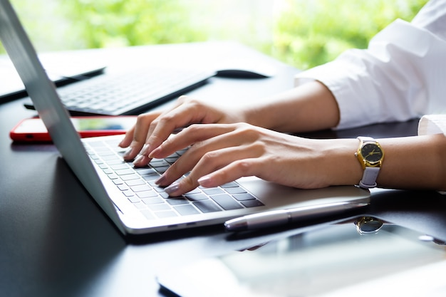 Female hand typing on keyboard of laptop Free Photo