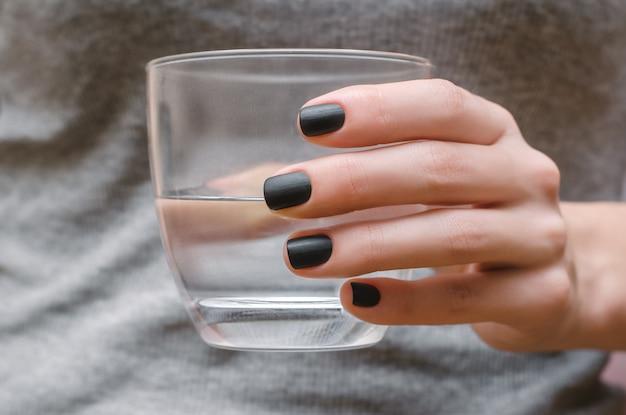Female hand with black matte nail design. Premium Photo