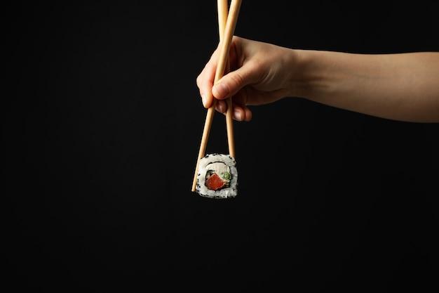 Женская рука с палочками для еды держать суши ролл на черной поверхности. японская еда Premium Фотографии