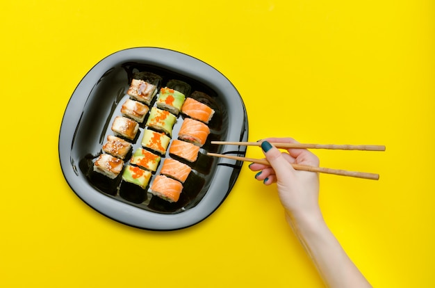 Female hand with chopsticks and plate with various sushi rolls. top view Premium Photo