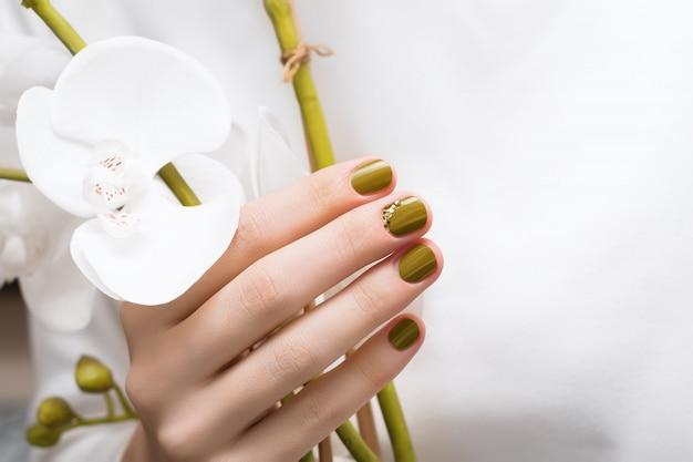 Женская рука с зеленым дизайном ногтя, концом вверх. Бесплатные Фотографии