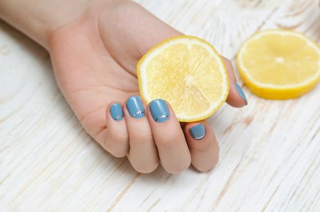 Female hand with light blue nail art holding lemon. Premium Photo