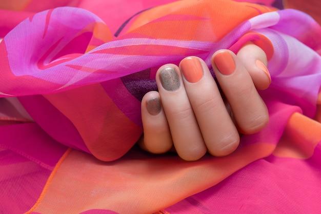 オレンジとグレーのネイルデザインと女性の手。 Premium写真