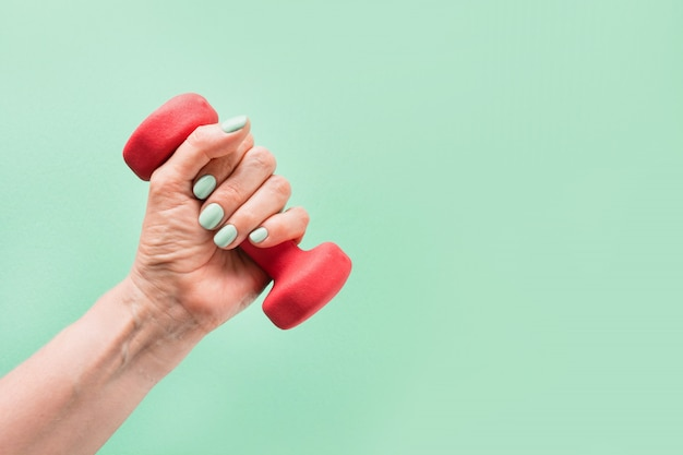 Female hand with red dumbbell on green background sport fitness equipment Premium Photo