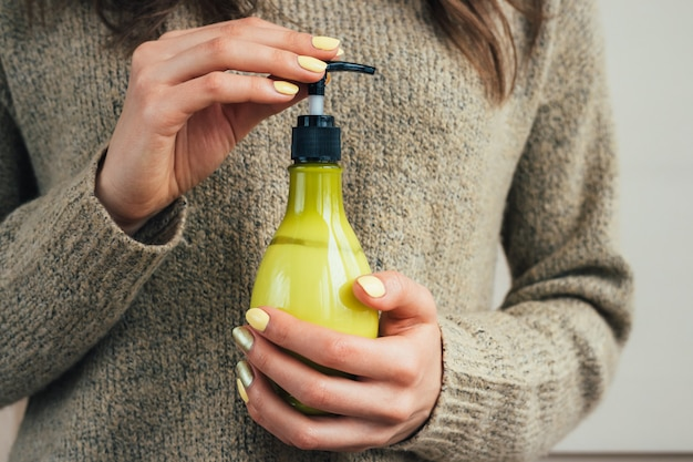 Female hand with a yellow manicure holding green bottle with cosmetic cream Premium Photo