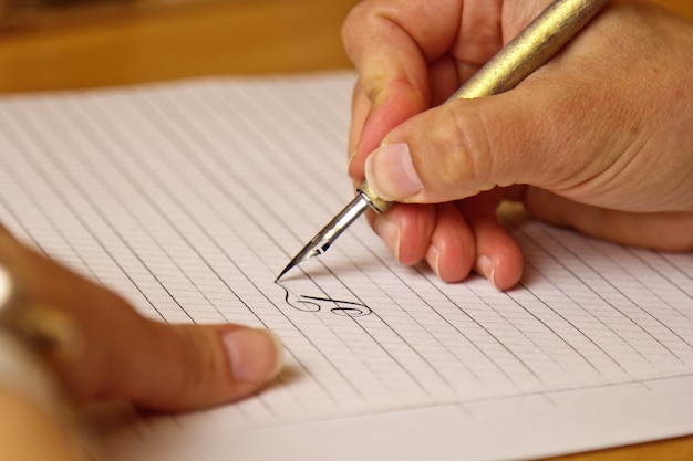 Female hand writes with an ink pen on a white paper sheet with stripes. Premium Photo