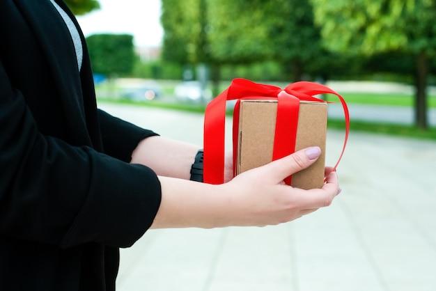 女性の手が贈り物を持っています。赤いリボンとタグが付いたクラフトボックスに入っています。閉じる。外側。美しい朝市の自然。休日の概念、父の日、母の日、誕生日、ウェディング Premium写真