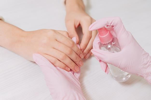 Женские руки заделывают. руки в розовых резиновых перчатках обработайте кожу рук антисептиком. Premium Фотографии