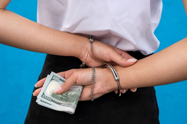 Female hands in handcuffs hold dollars isolated on blue.  prisoner or arrested Premium Photo