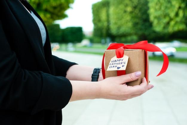 女性の手は父の日にお父さんへのプレゼントを持っています。赤いリボンとタグが付いたクラフトボックスに入っています。閉じる。外側。美しい朝市の自然。休日のコンセプトです。 Premium写真