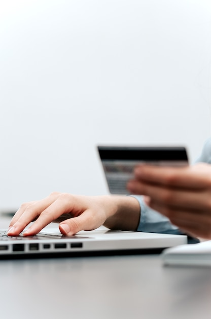 Female hands hold credit card, pressing buttons and making online purchase closeup. Premium Photo
