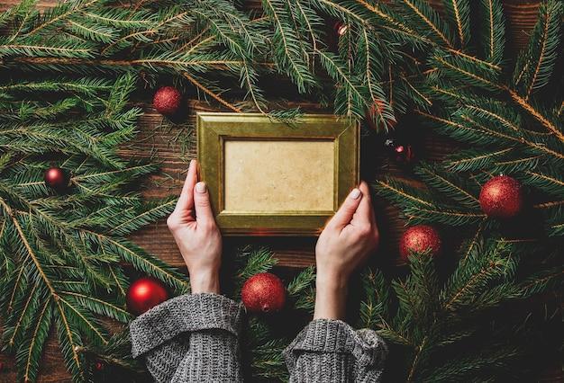 Женские руки держат фоторамку рядом с рождественским украшением Premium Фотографии