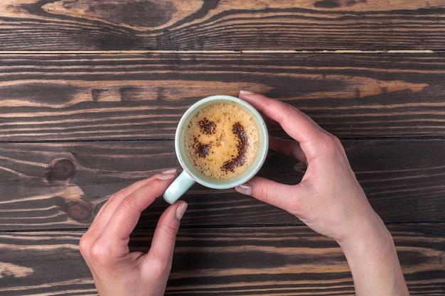 Женские руки, держа чашку кофе с пеной над деревянным столом. с шоколадной посыпкой Premium Фотографии
