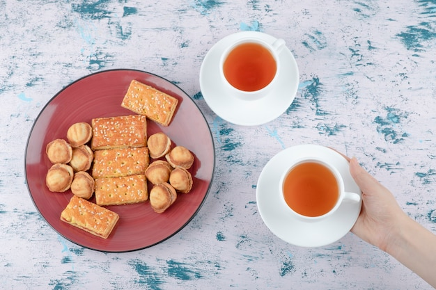 練乳とショートブレッドナッツとお茶のカップを保持している女性の手。 無料写真