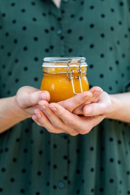 Женские руки держат домашнее веганское сырое абрикосовое варенье в стеклянной банке Бесплатные Фотографии